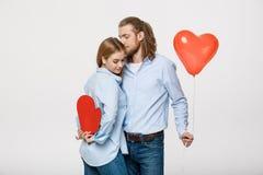 Portrait du jeune homme et de la femme tenant un ballon et un papier en forme de coeur Photographie stock libre de droits