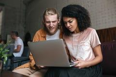 Portrait du jeune homme et de la fille regardant amazedly l'ordinateur portable Fille d'afro-américain avec les cheveux bouclés f Images stock