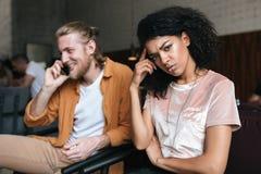 Portrait du jeune homme et de la fille s'asseyant dans le restaurant Fille bouleversée d'Afro-américain avec les cheveux bouclés  Photos libres de droits