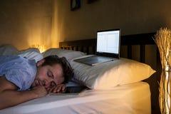 Portrait du jeune homme fatigué caucasien s'étendant sur le lit utilisant l'ordinateur portable pendant longtemps Photographie stock libre de droits