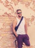 Portrait du jeune homme frais attirant se penchant sur le vieux mur de briques images libres de droits