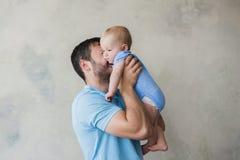 Portrait du jeune homme heureux tenant son bébé doux Photographie stock