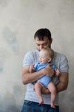 Portrait du jeune homme heureux tenant son bébé doux Image stock