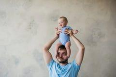 Portrait du jeune homme heureux tenant son bébé doux Photos libres de droits