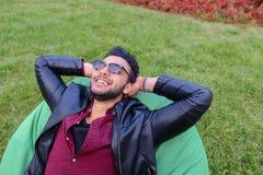 Portrait du jeune homme masculin arabe, étudiant Lies sur la chaise, Smilin photographie stock libre de droits