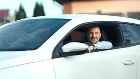 Portrait du jeune homme réussi heureux d'affaires s'asseyant sur la roue de la voiture de sport blanche moderne clips vidéos