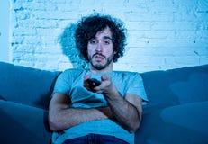 Portrait du jeune homme sans sommeil ennuy? s'asseyant sur le divan regardant la TV la nuit photo stock