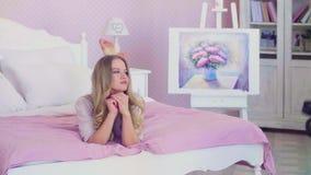 Portrait du jeune joli modèle posant dans le lit banque de vidéos