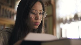Portrait du jeune livre de lecture asiatique de femme se reposant à la table dans la bibliothèque banque de vidéos