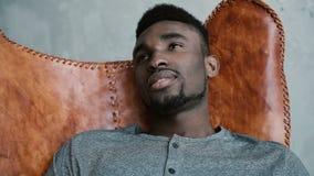 Portrait du jeune mâle africain s'asseyant dans la chaise en cuir, pensant à quelque chose et au sourire L'homme regarde pensivem Photo stock