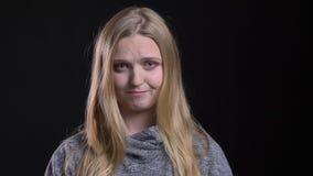 Portrait du jeune modèle aux cheveux droits blond observant dans la caméra avec la confusion et timidité sur le fond noir clips vidéos