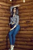 Portrait du jeune modèle aux cheveux foncés sexy utilisant de hauts-waisted jeans maigres, attachée chemise rayée, foulard et esp image stock