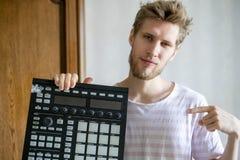 Portrait du jeune producteur barbu de bruit d'homme tenant le contrôleur et les écouteurs f du Midi photographie stock