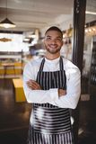 Portrait du jeune serveur beau de sourire se tenant avec des bras croisés Photos stock