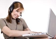 Portrait du joli opérateur d'appel souriant et dactylographiant sur le dessus de recouvrement Images stock