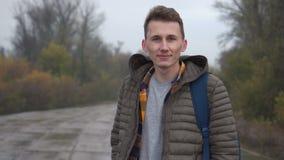 Portrait du mâle caucasien beau regardant à la caméra, position élégante d'homme extérieure dans le mouvement lent banque de vidéos