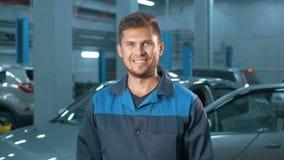 Portrait du mécanicien de voiture de sourire professionnel travaillant dans le service des réparations automatique moderne Images libres de droits