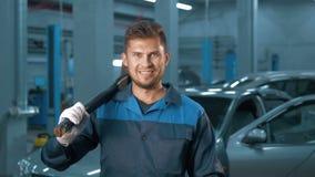 Portrait du mécanicien de voiture de sourire professionnel travaillant dans le service des réparations automatique moderne Photos libres de droits