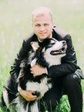 Portrait du marié de sourire étreignant le chien mignon dans le domaine Photographie stock