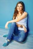 Portrait du modèle de sourire femelle de style d'adolescent se reposant sur le floo Image libre de droits