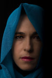 Portrait du Moyen-Orient de femme semblant triste avec l'artiste bleu de hijab Photo stock