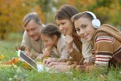 Portrait du père, de la mère et des enfants faisant des devoirs en parc photographie stock libre de droits