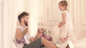 Portrait du père de sourire et riant et de sa fille ayant l'amusement combattant avec des oreillers banque de vidéos