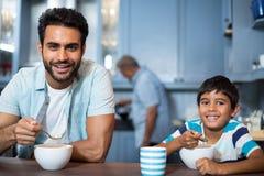 Portrait du père et du fils prenant le petit déjeuner avec l'homme à l'arrière-plan Image libre de droits