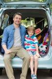 Portrait du père et du fils s'asseyant dans le tronc de voiture images stock