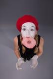 Portrait du pantomime assez féminin mangeant un rose savoureux Images libres de droits