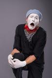 Portrait du pantomime masculin dans la tête rouge et avec le blanc Photo stock