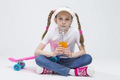 Portrait du pare-soleil de port de fille blonde assez caucasienne se reposant sur le plancher avec la tasse de jus Photo stock