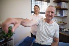 Portrait du patient masculin supérieur de sourire s'asseyant avec l'épaule de examen de docteur féminin Images libres de droits