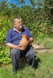 Portrait du paysan supérieur ukrainien s'asseyant sur un rondin et prenant une cruche antique d'argile photographie stock libre de droits