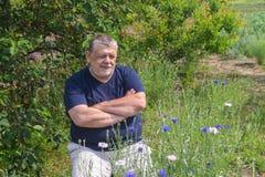 Portrait du paysan ukrainien supérieur s'asseyant dans un jardin de ressort et des fleurs admiratives de Centaurea Photos libres de droits