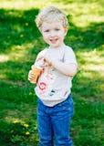 Portrait du petit enfant en bas âge caucasien blond drôle mignon de fille d'enfant se tenant dans les bulles de savon de soufflem Image stock
