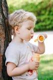 Portrait du petit enfant en bas âge caucasien blond drôle mignon de fille d'enfant se tenant dans les bulles de savon de soufflem Images stock