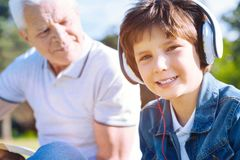 Portrait du petit garçon dans des écouteurs souriant dans l'appareil-photo Image stock