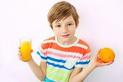 Portrait du petit garçon heureux buvant du jus d'orange images stock