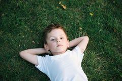 Portrait du petit garçon mignon se trouvant sur l'herbe verte Photo stock