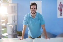 Portrait du physiothérapeute masculin tenant le lit proche de massage photo libre de droits