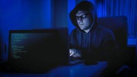 Portrait du pirate informatique masculin dans le hoodie se reposant dans la chambre noire et travaillant sur l'ordinateur Images libres de droits