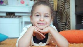 Portrait du plan rapproché du visage d'une fille mignonne La belle petite fille regarde la caméra et les sourires gentiment clips vidéos