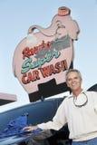Portrait du propriétaire mûr de la station de lavage se tenant au-dessous de l'enseigne avec le véhicule Images stock
