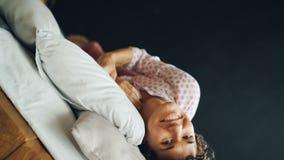 Portrait du roulement gai de brune de fille dans le double lit avec le sourire heureux ayant l'amusement et regardant l'appareil- clips vidéos