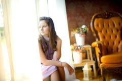 Portrait du ` s de fille à une fenêtre Photos stock