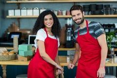Portrait du serveur et de la serveuse de sourire se penchant au compteur Photographie stock