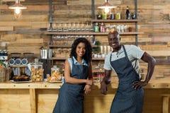 Portrait du serveur et de la serveuse de sourire se penchant au compteur Photo libre de droits