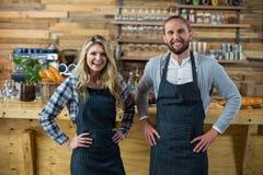 Portrait du serveur et de la serveuse se tenant avec la main sur la hanche au compteur Image stock