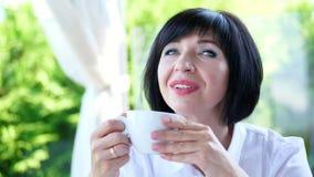 Portrait du sourire agréable, belles vraies 40 années heureuses de femme d'Ukrainien un café potable de femme, thé, d'a banque de vidéos